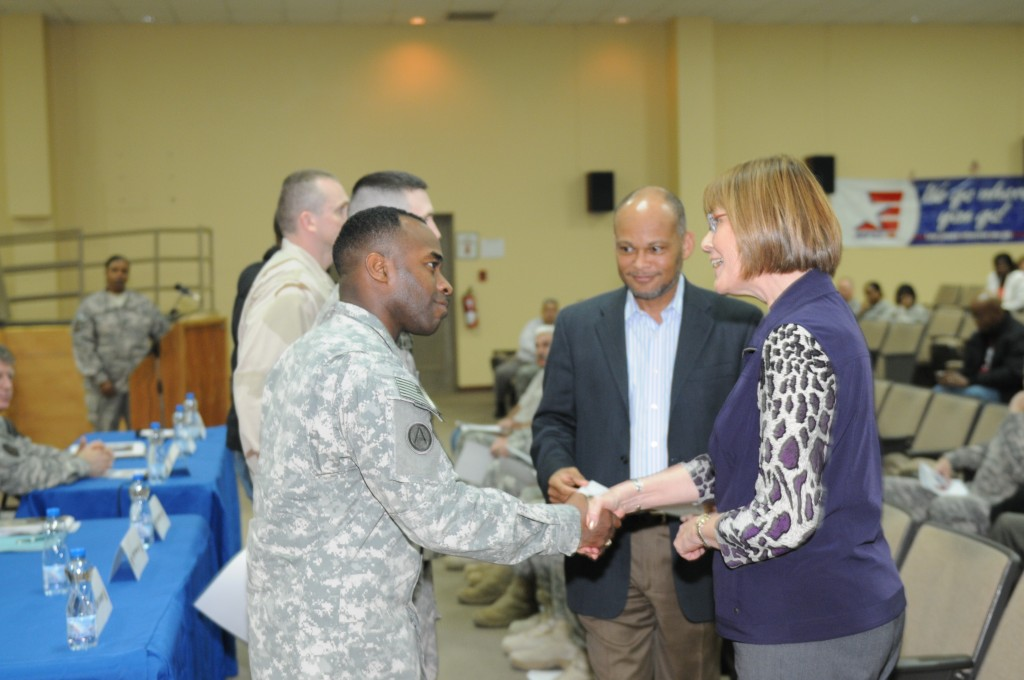 Carol Lowman, executive director, Army Contracting Command, and Charlie E. Williams, second from right, director, Defense Contracting Management Agency, present an award to U.S. Army Sgt. Errol Worme, with Area Support Group-Kuwait, during a town hall meeting and recognition event concerning Department of Defense contractors and contractor representatives at Camp Arifjan, Kuwait, Feb. 8, 2012. Contractors write, analyze and award contracts within Third U.S. Army's area of responsibility. The 408th Contracting Support Brigade hosted the meeting. (U.S. Army photo by Staff Sgt. Regina Machine/Released)